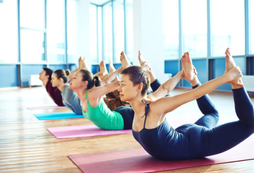 Group of young people relaxing and practicing in yoga